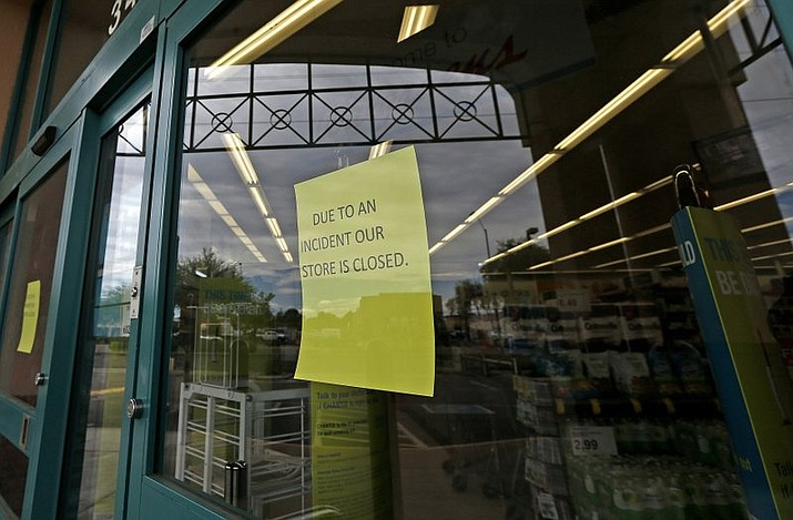 Signs posted at the entrance of a local Walgreens let possible customers know that the store remains closed Wednesday, Aug. 2, 2017, in Phoenix, after a customer at the drugstore shot and killed a man who was attempting to rob the pharmacy Tuesday night, according to police. (AP Photo/Ross D. Franklin)