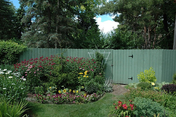 Decorative fences are an effective way to hide composting stations conveniently tucked behind gardens in the landscape. (Melinda Myers, LLC/Courtesy)