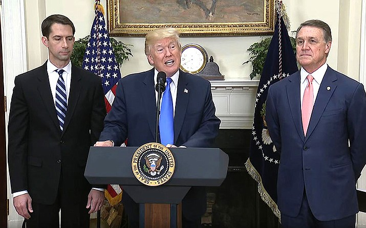 President Donald Trump threw his support behind a bill sponsored by Republican Sens. Tom Cotton of Arkansas, left, and David Perdue of Georgia, that could cut legal immigration in half while setting up a merit-based immigration system.