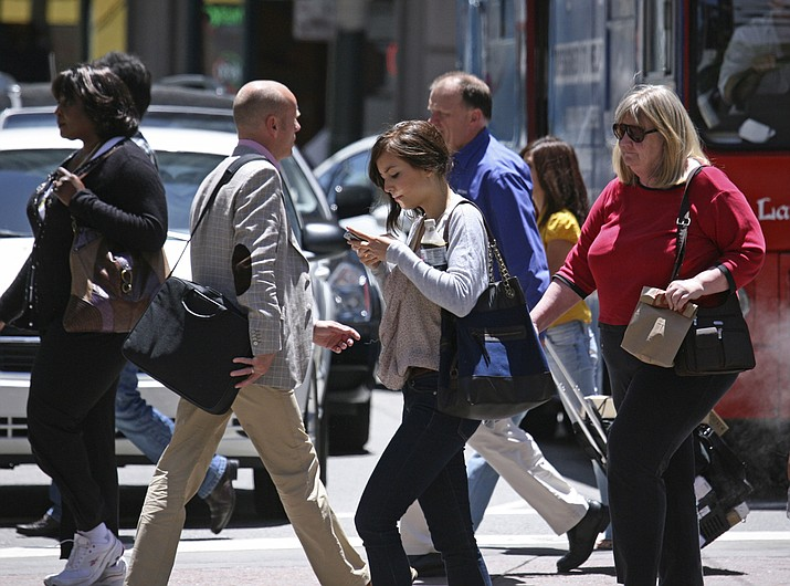 While using a cell phone while driving has triggered the most alarm bells and prompted laws in many states, experts say pedestrians are also suffering the consequences of mobile distraction tripping on curbs, walking into traffic, even stepping into manholes as they chat or type while walking. (AP File Photo/Ben Margot)