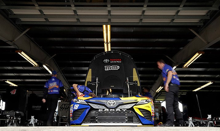 Crew members work on the car of Kyle Busch before practice for Sunday's NASCAR Cup Series auto race, Saturday, Aug. 5, 2017, in Watkins Glen, N.Y. (AP Photo/Matt Slocum)
