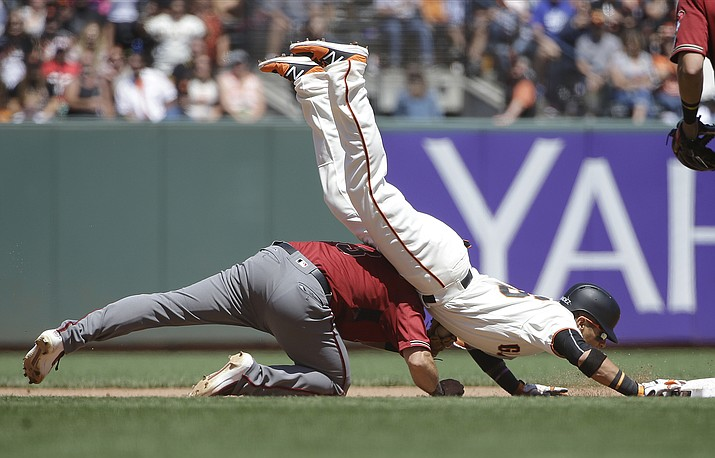 San Francisco's Gorkys Hernandez, top, dives safely over Arizona second baseman Daniel Descalso on his double during the fifth inning of a baseball game in San Francisco, Sunday, Aug. 6. (Jeff Chiu/AP)