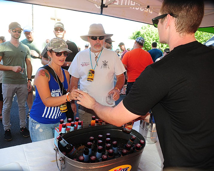 Nicole Garrett and Kevin Gordon get their Deschutes beers at the 4th annual Mile High Brewfest on Cortez Street in Prescott Saturday afternoon.
