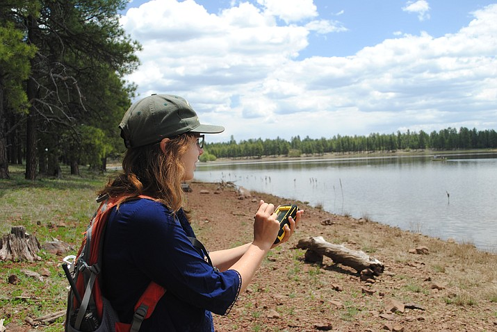 Recreation intern Mary Bielamowicz maps a trail near a lake on the Williams Ranger District.