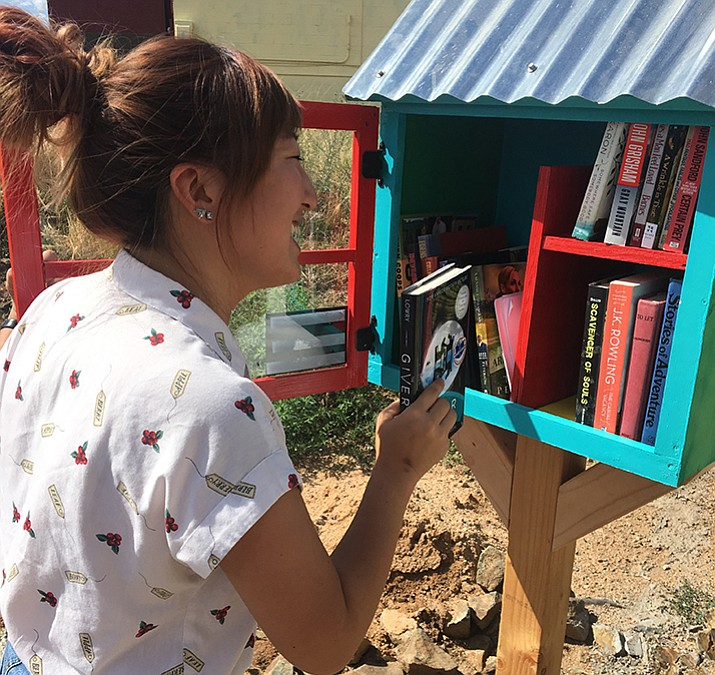 Prescott Valley Public Library Adult Services Libarian Jennifer Kim places a book into the library's new Little Free Library. (courtesy/Jennifer Kim)
