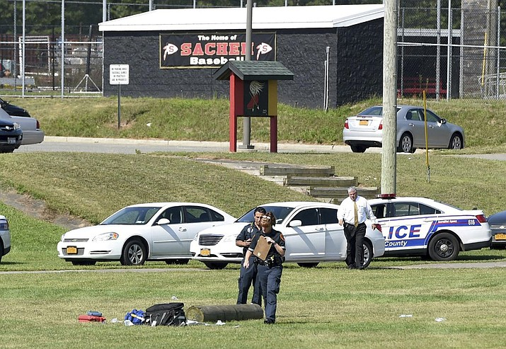 Suffolk County police work on the athletic field at Sachem High School East in Farmingville, N.Y., where a teenage football player was fatally injured during a drill earlier in morning, Thursday, Aug. 10, 2017. (James Carbone/Newsday via AP)