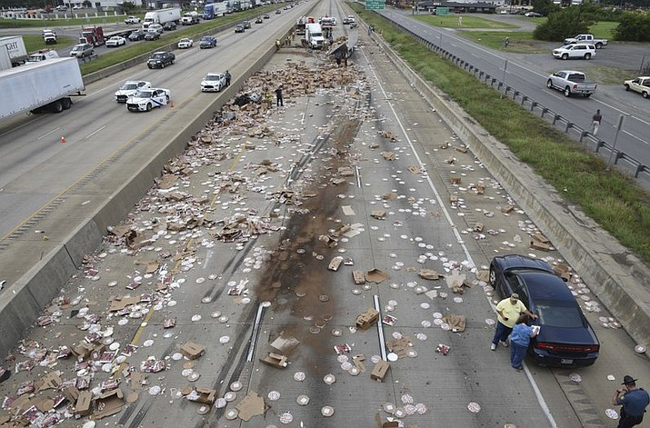 An 18-wheeler containing DiGiorno and Tombstone frozen pizzas scraped a bridge support and sliced open its trailer Wednesday, spilling the pies across Interstate 30 in front of the Arkansas Department of Transportation office just south of Little Rock. (Rusty Hubbard, Arkansas Department of Transportation via AP)