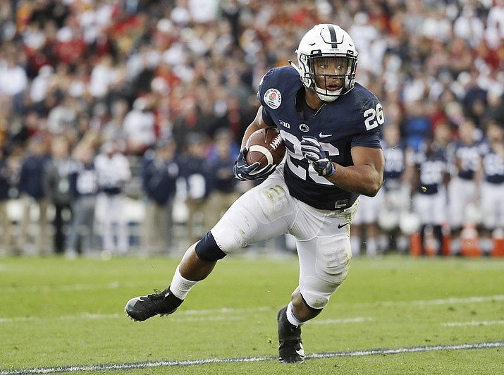 In this Jan. 2, 2017, file photo, Penn State Nittany Lions running back Saquon Barkley (26) looks for room to run against the USC Trojans during the first half of the Rose Bowl NCAA college football game, in Pasadena, Calif. Defending Big Ten champion Penn State returns a Heisman Trophy candidate at running back and a record-setting quarterback, and the Nittany Lions generally are regarded as one of the 10 best teams in the country. (Doug Benc/AP, File)