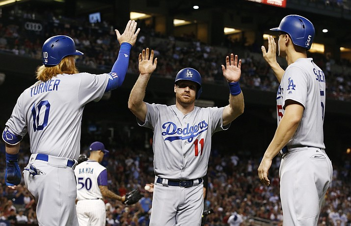 Los Angeles Dodgers' Logan Forsythe (11) celebrates with Justin Turner (10) and Corey Seager, right, after all three scored against the Arizona Diamondbacks on a double by Enrique Hernandez during the first inning Thursday, Aug 10, 2017, in Phoenix. (Ross D. Franklin/AP)