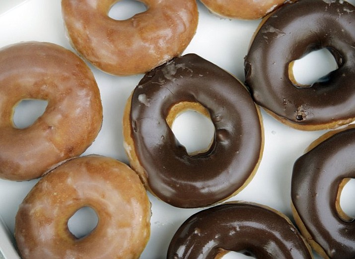 Krispy Kreme doughnut announced Aug. 9, 2017, that it's giving its signature glazed treats a chocolate sheen for the first time ever in honor of the Aug. 21 eclipse. (AP Photo/Chuck Burton, File)