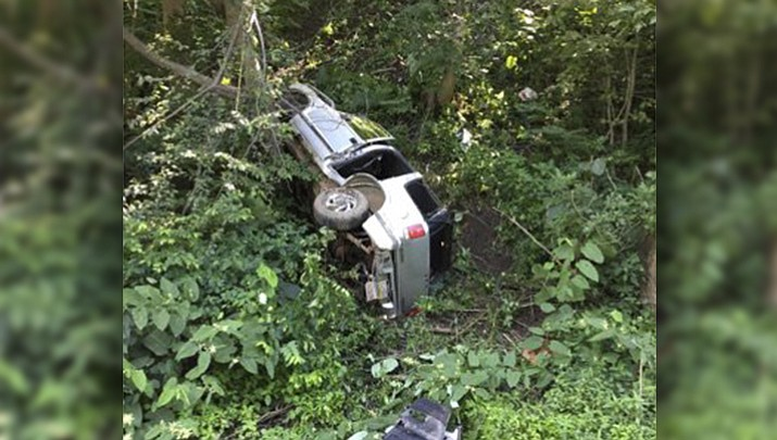 "An SUV which contained a toddler inside lies on its side after rolling down a 100-foot-high hill, in Vandergrift, Pa. Pennsylvania police said a 2-year-old boy ""was happy as could be"" and wasn't injured after he and the SUV rolled down the hill. (Joseph Gray/Vandergrift Police Department via AP)"