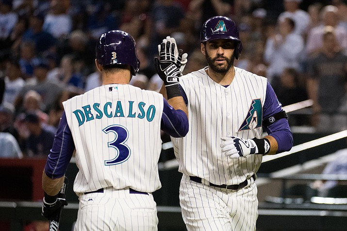 J.D. Martinez high fives Daniel Descalso after hitting a solo home run in the seventh inning of the Arizona D-backs' 8-7 loss to the Dodgers Thursday.