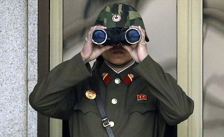 In this file photo, a North Korean soldier looks at the southern side through a pair of binoculars at the border village of Panmunjom, which has separated the two Koreas since the Korean War, in Paju, north of Seoul, South Korea. Threatening to fire a volley of missiles toward a major U.S. military hub - and the home to 160,000 American civilians - may seem like a pretty bad move for a country that is seriously outgunned and has an awful lot to lose. But pushing the envelope, or just threatening to do so, is what North Korea does best.