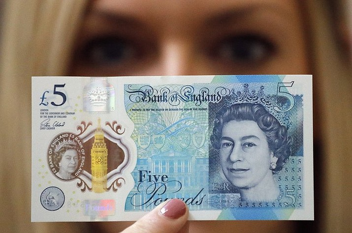 A Bank of England employee shows the new five pound note at the Bank of England Museum in London. The Bank of England has rejected calls to scrap new banknotes that contain traces of animal fat. The bank said Thursday, Aug. 10, 2017, it will continue to issue polymer notes that contain tallow, a rendered form of animal fat. (AP Photo/Frank Augstein, File)