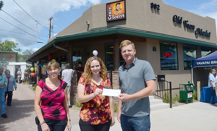 Crazy Tony's Operations Manager Stephen Cook passes the check to Kellie Wilson, executive director of the Old Town Mission in Cottonwood. VVN/Vyto Starinskas