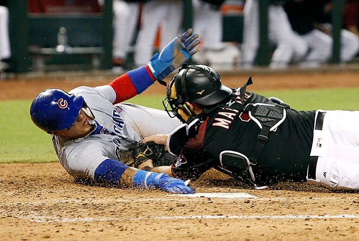Chicago Cubs' Javier Baez, left, reaches for the plate as he is tagged out by Arizona Diamondbacks catcher Jeff Mathis while trying to score from third on an infield ground ball by teammate Albert Almora Jr. during the fifth inning of a baseball game, Saturday, Aug. 12, in Phoenix. The call was upheld by replay after the Cubs challenged the play. (Ralph Freso/AP)