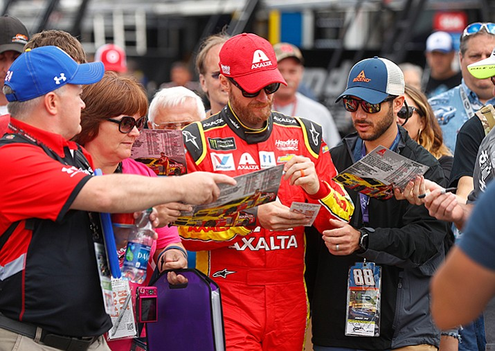 Dale Earnhardt Jr. signs autographs in the garage before practice for the NASCAR Cup Series auto race in Brooklyn, Mich., Saturday, Aug. 12, 2017. (AP Photo/Paul Sancya)