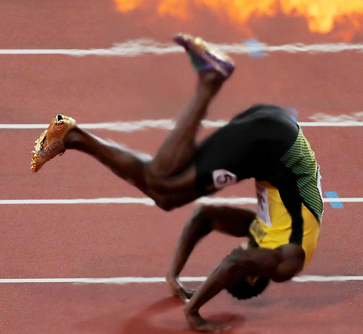 Fireworks for the winner go off as Jamaica's Usain Bolt falls after suffering an injury, during the men's 4x100-meter final at the World Athletics Championships in London Saturday, Aug. 12. (Frank Augstein/AP)