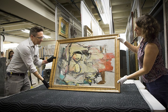 """Willem de Kooning's """"Woman-Ochre"""" is readied for examination by Nathan Saxton, right, an exhibitions specialist, and Kristen Schmidt, a registrar, in Phoenix. More than three decades after thieves made off with the valuable painting from the University of Arizona Museum of Art, officials have recovered the long sought piece from an antique dealer in New Mexico. (University of Arizona via AP)"""