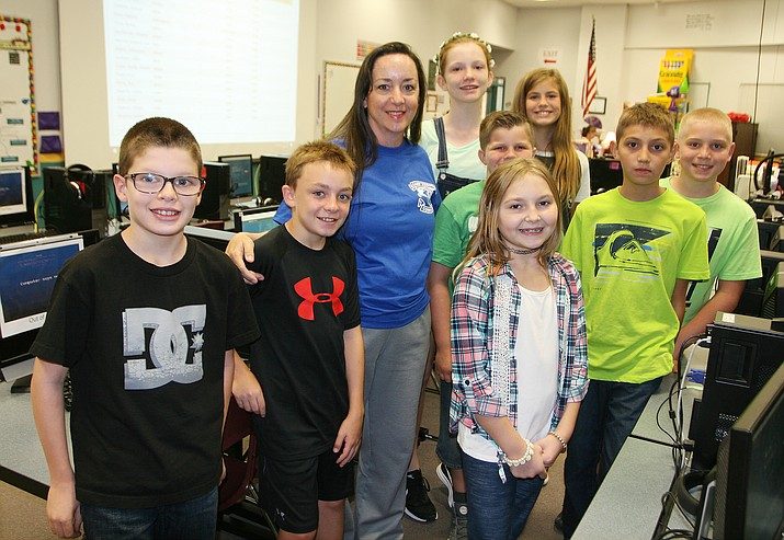 Peggy Dickey poses for a photograph with students in Camp Verde Unified School District's 5th Day programs. Recently, Dickey was named the district's 5th Day programs coordinator. (Photo by Bill Helm)