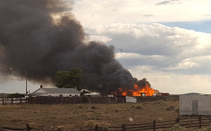 A fire rages at an unidentified residence north of Williams in July. Many rural residences lie outside designated fire districts in northern Arizona.