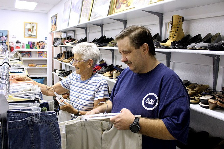 James Haseltine, treasurer and web designer for St. Vincent de Paul Society in Kingman, helps Rosie Gaia hang clothes on the rack at St. Vincent Thrift Store. Haseltine recently launched a web site for St. Vincent de Paul that gives information on client services, available resources, donor pickup requests and links to other agencies.