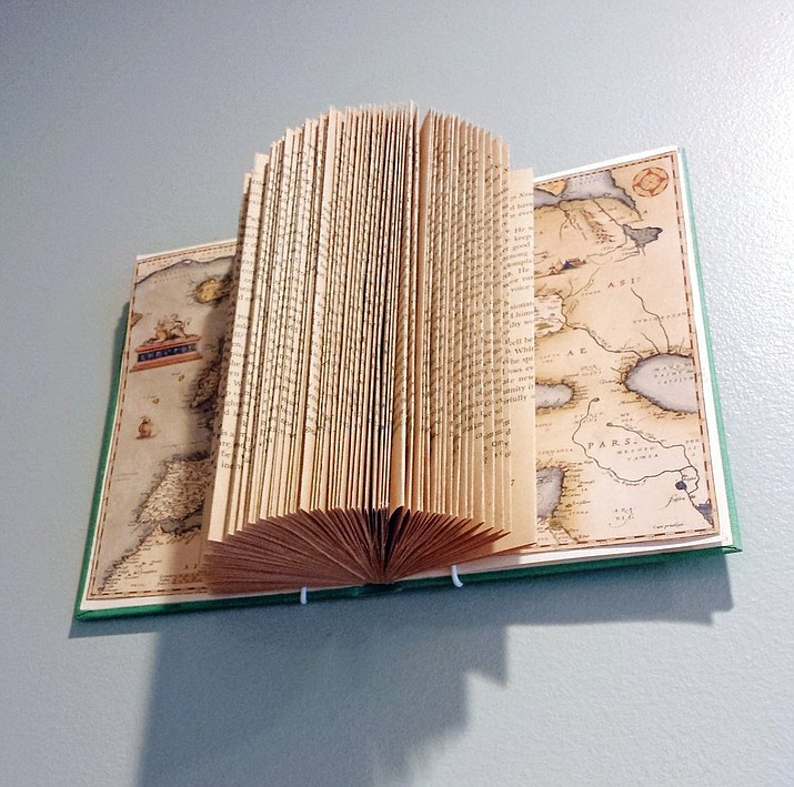 This undated photo provided by Candice Caldwell shows book folding projects hanging on the wall of her Chicago home.  Turning a book into three-dimensional sculpture can create a  beautiful conversation piece.(Candice Caldwell via AP)