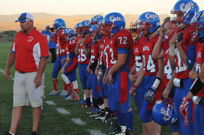 Mayer football coach Mike Gutierrez, left, surveys the field as the Wildcats prepare to face Greyhills Academy in a Week Zero game Friday, Aug. 18, 2017, in Spring Valley. Mayer cruised to a 56-0 victory to move its record to 1-0 on the young 2017 season. (Doug Cook/Courier)