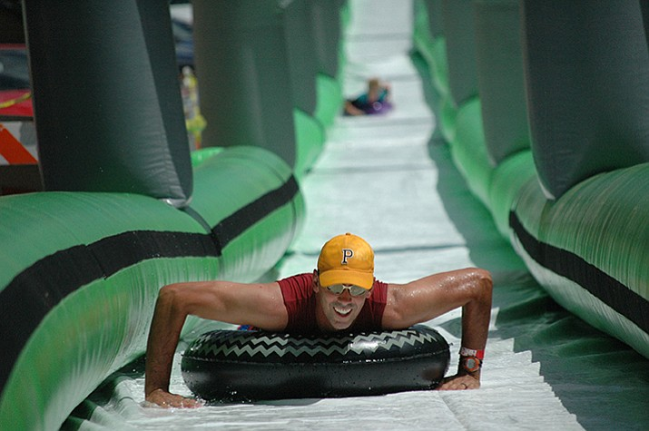 Brian Patterson slides down the 675-foot water slide on Union Street at the 2017 Northern Arizona Monsoon Festival. (Jason Wheeler/Courier)