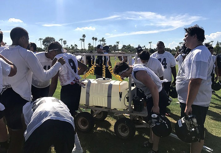 McClintock High School football players take a break during the 110-degree heat. (Photo by Faith Phares/Cronkite News)