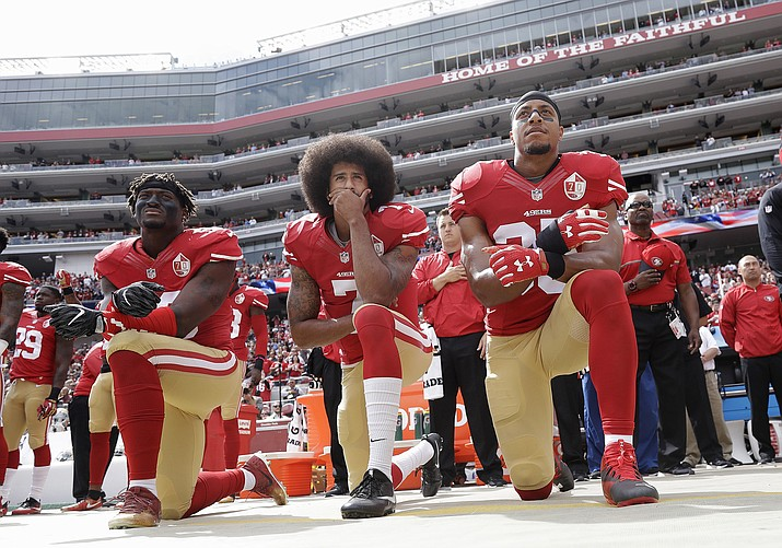 In this Oct. 2, 2016, photo, from left, San Francisco 49ers outside linebacker Eli Harold, quarterback Colin Kaepernick, center, and safety Eric Reid kneel during the national anthem before an NFL football game against Dallas (Marcio Jose Sanchez, AP, file)