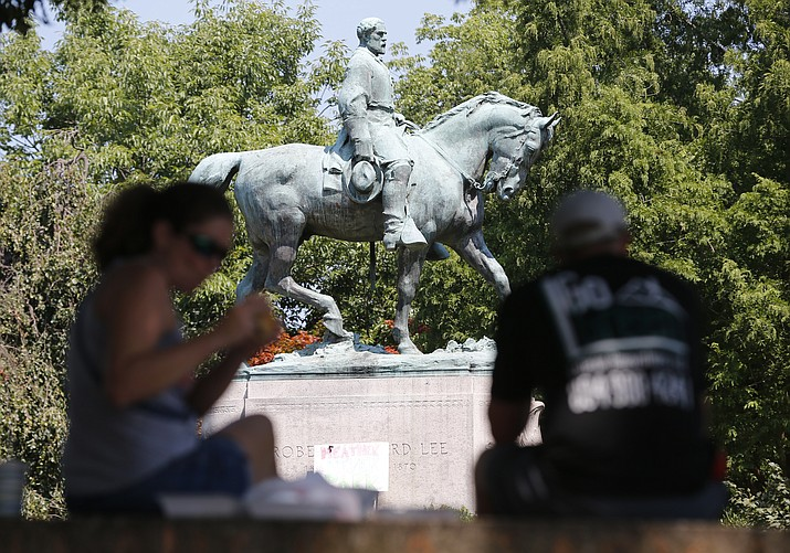 A couple have a picnic lunch on a bench in front of the statue of Confederate General Robert E. Lee a week after protest violence at the park in Charlottesville, Va., Saturday, Aug. 19. (Steve Helber/AP)