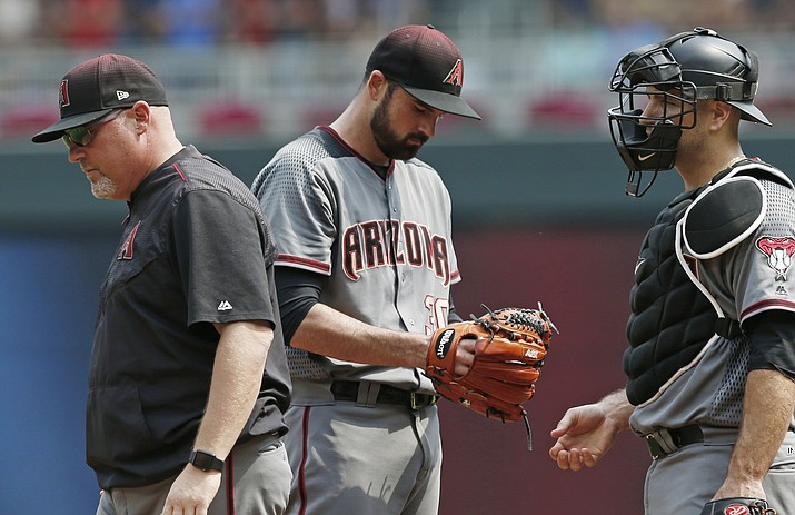 Arizona pitcher T.J. McFarland, center, stands quietly after a visit to the mound by pitching coach Mike Butcher, left, during Sunday's game against the Minnesota Twins. (Jim Mone/AP)