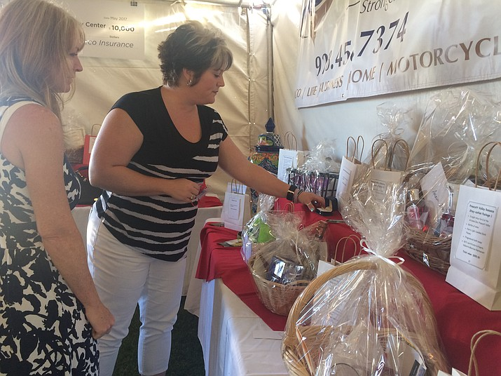 Michelle Medina, left, and Amy Knight check out one of the items on the raffle table at the third annual Hope Still Floats, a fundraiser for the Yavapai Family Advocacy Center, at the Prescott Club at StoneRidge on Saturday, Aug. 19. (Jason Wheeler/Courier)