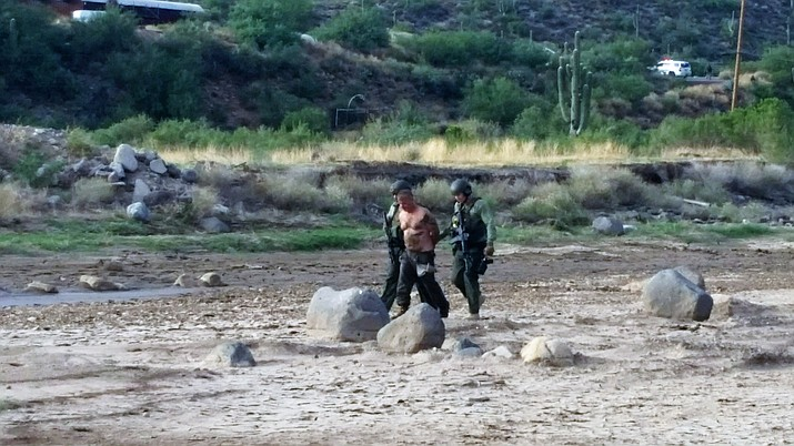 Officers lead Scott Albert Wayne, 54, away from the riverbed in which he was found Sunday afternoon. He was arrested after claiming he was carrying an explosive device in his pants pockets. (YCSO/Courtesy)