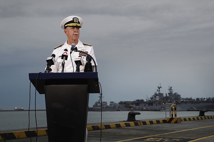 Commander of the U.S. Pacific Fleet, Scott Swift answers questions during a press conference with the USS John S. McCain and USS America docked in the background at Singapore's Changi naval base on Tuesday, Aug. 22, 2017, in Singapore. The focus of the search for 10 U.S. sailors missing after a collision between the USS John S. McCain and an oil tanker in Southeast Asian waters shifted Tuesday to the damaged destroyer's flooded compartments. (AP Photo/Wong Maye-E)