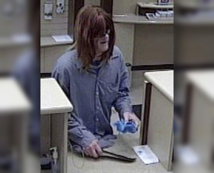 This Monday, Aug. 21, 2017, frame from surveillance video provided by the FBI Pittsburgh Division shows a bank robber who wore an unkempt woman's wig to disguise himself at a Dollar Bank branch in Pittsburgh's South Side. (FBI Pittsburgh Division and the Pittsburgh Bureau of Police via AP)