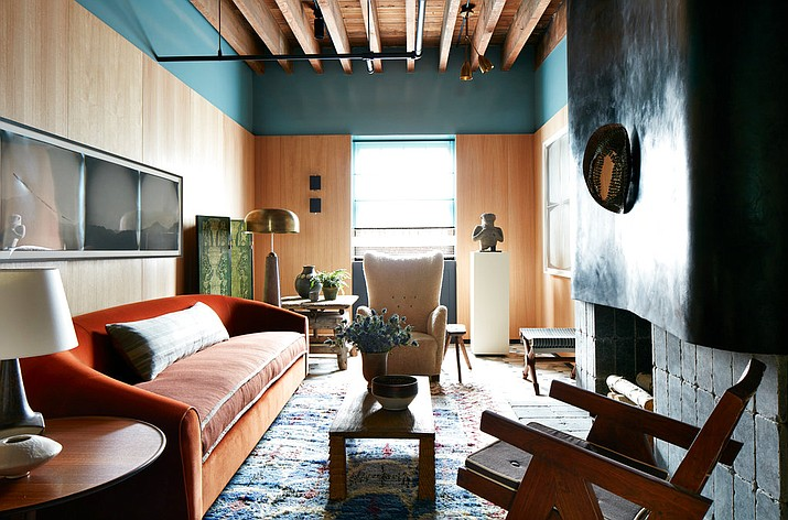 This April 2017 photo provided by Stephen Kent Johnson shows Neal Beckstedt's space at the Kip's Bay Show House in New York. This spring Beckstedt clad his space in oak veneer, but brought it within about a foot of the ceiling, then applied a thick band of teal lacquer the rest of the way. Bold hues and warm textures set the stage for home décor that's got drama, yet is very livable. (Stephen Kent Johnson via AP)