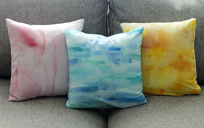 This Aug. 20, 2017, photo in Hopkinton, N.H., shows three pillows created using different techniques for achieving a watercolor effect on fabric. Getting artwork off the walls and onto a sofa is as easy as painting fabric and using it to cover throw pillows. (AP Photo/Holly Ramer)