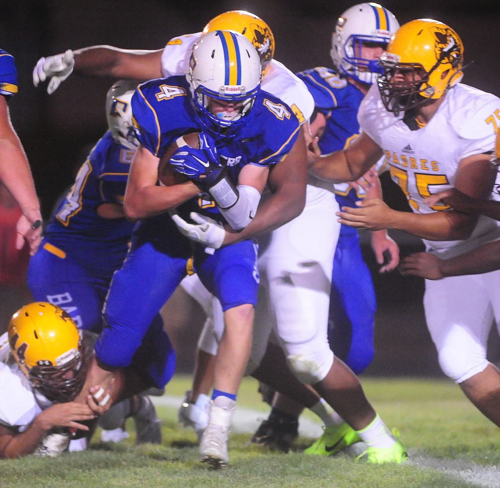 Prescott's Aaron Greene gets stacked up after a gain as the Badgers take on the Marcos de Niza in Prescott Friday, August 25. (Les Stukenberg/The Daily Courier)