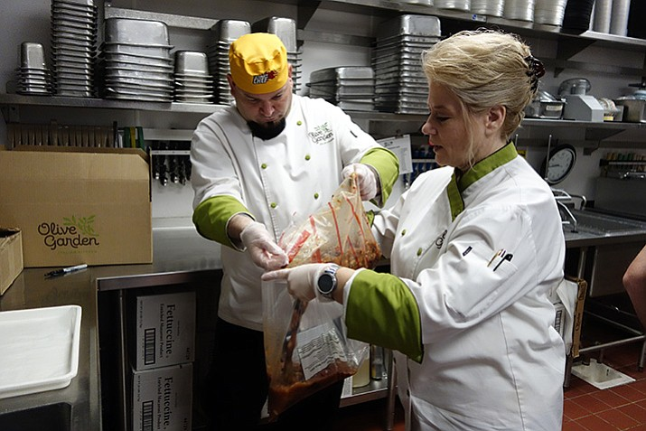 Olive Garden employees Tiffany Talbot and Seth Goldstein package unused soup to be donated to a local hunger relief organization. (Max Efrein/Courier)