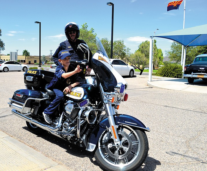 "Nathan Calderon fires up Officer Chaz Truver's police motorcycle before a short ride around the parking lot. Calderon also got to pull over a ""speeder"" and issue a ticket."
