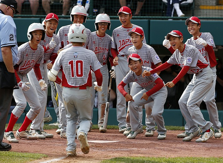 Japan's Keitaro Miyahara (10) is greeted by teammates after hitting a solo home run off Lufkin, Texas' Chip Buchanan in the fourth inning of the Little League World Series Championship baseball game in South Williamsport, Pa., Sunday, Aug. 27, 2017. (Gene J. Puskar/AP).