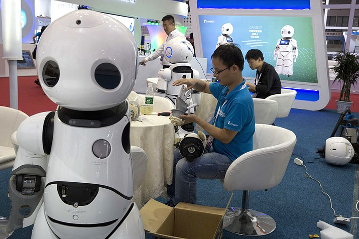 A worker repairs the arm of a robot before the opening of the World Robot Conference held in Beijing, China last week. Just as automation has begun to do jobs previously seen as uniquely suited for humans, robots will assist the elderly in the very near future. (AP Photo/Ng Han Guan)