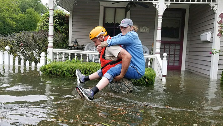 A Texas National Guard soldier carries a woman out of a flooded building during rescue operations in Houston.