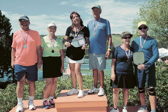 Atop the podium stands Denise Ashworth, left, and Bob Truckenmiller, as they claimed a gold medal in the age 70-plus division at the Prescott Lakes Senior Pickleball tournament Aug. 20 in Prescott. (Bob Atherton/Courtesy)
