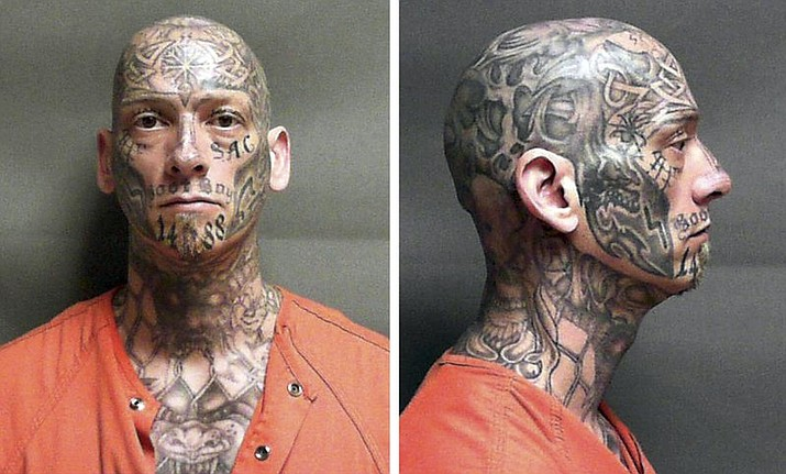 Eric Judkins, an inmate at a halfway house in Manchester, N.H., failed to return to the facility Monday night, Aug. 28, 2017. Officials are seeking the public's help in finding the heavily tattooed escaped inmate, with designs covering his shaved head, face, neck, chest, arm and hands. (U.S. Marshal's Office via AP)