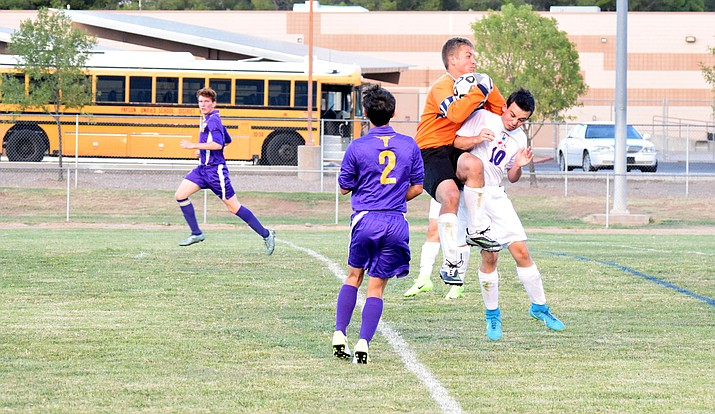 Camp Verde sophomore Kelton O'Grady runs into the Payson goalkeeper during the Cowboys' 8-1 win on Tuesday at home. The Cowboys have a half a dozen strikers on their roster (VVN/James Kelley)