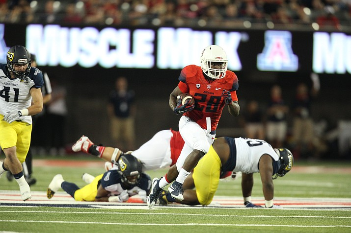 Arizona's Nick Wilson runs the ball against NAU in 2015. The Wildcats won 77-13, setting the single-game scoring record and total offense standard (792 yards). (Photo courtesy Arizona Athletics)