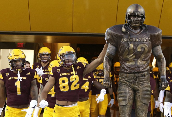 Arizona State's Josh Pokraka (82) and teammates touch the Pat Tillman statue before a game against New Mexico State on Thursday, Aug. 31, 2017, in Tempe. The Tillman statue was unveiled Wednesday, Aug. 30, 2017. (Rick Scuteri/AP)